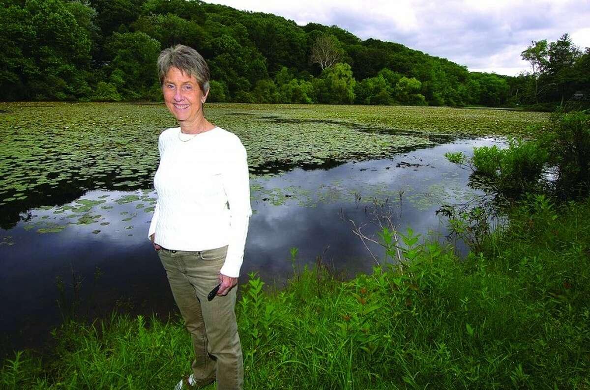 Hour Photo/ Alex von Kleydorff. Anne Deware stands on the bank of Horseshoe Pond in Wilton