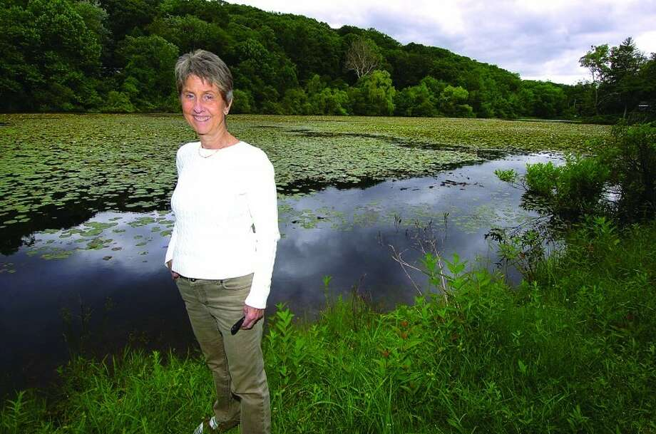 Hour Photo/ Alex von Kleydorff. Anne Deware stands on the bank of Horseshoe Pond in Wilton