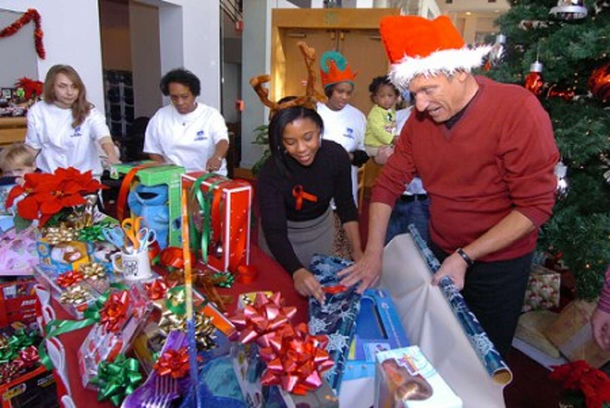 Photo/Alex von Kleydorff. Maury Povich wraps some holiday gifts in the lobby of the Stamford Media Center with help from At. Lukes Lifeworks Holiday Gift Collection Manager Takeia McAlister.