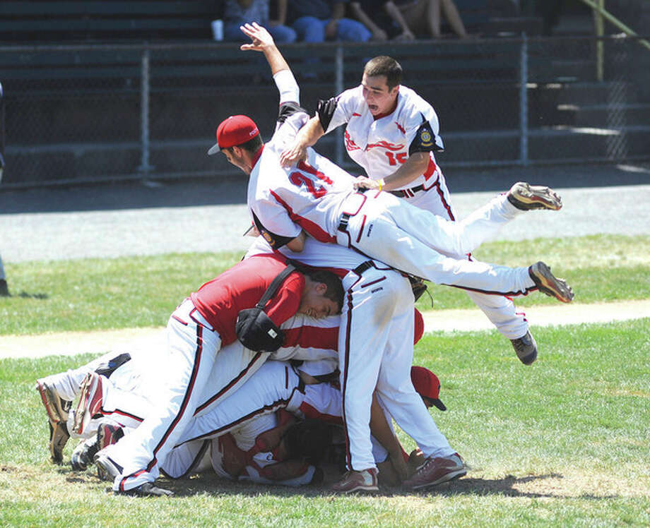 Hour Photo/John Nash - Members of the Norwalk Post 12 American Legion baseball team pile on to each other after winning the 2011 state championship with a 3-0 win over Branford at Muzzy Field in Bristol.