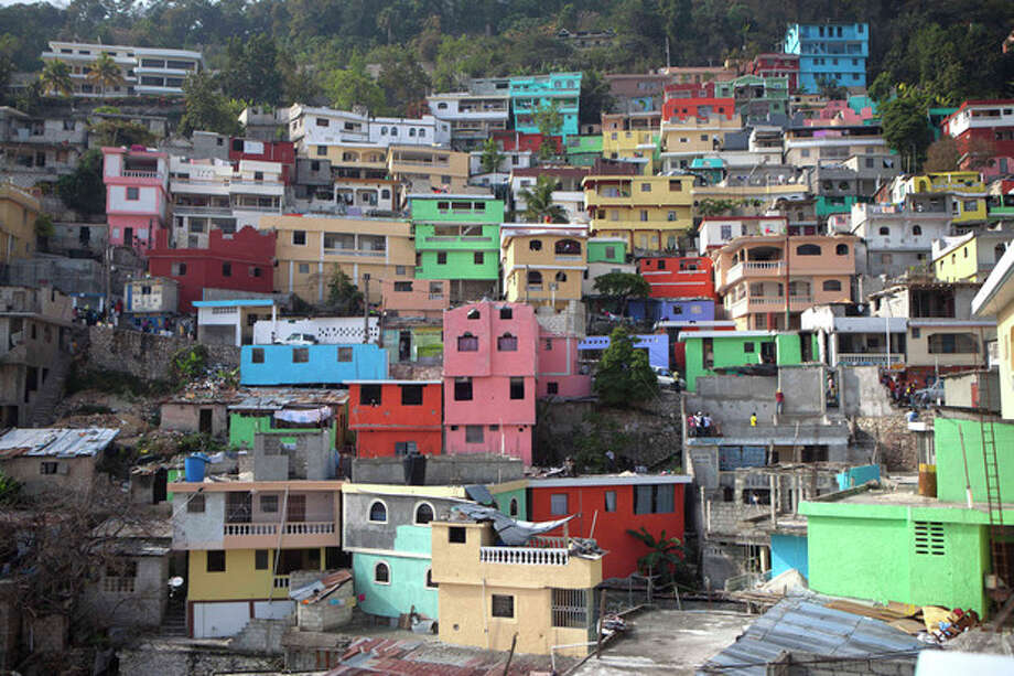"In this picture taken March 21, 2013, homes painted in bright colors cover a hill in Jalousie, a cinder block shantytown in Petionville, Haiti. Workers this month began painting the concrete facades of buildings in Jalousie slum a rainbow of colors, inspired by the dazzling ""cities-in-the-skies"" of well-known Haitian painter Prefete Duffaut, who died last year. (AP Photo/Dieu Nalio Chery) / AP"