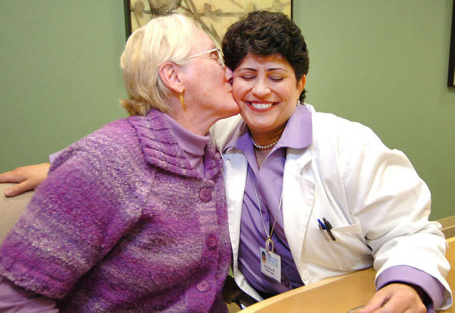 Hour Photo/Alex von Kleydorff. Annelise Lust whose husband suffered with Alezheimers disease, give a kiss to Dawn Pelazza R.N. with the 'Forget me Not' program offered at Visiting Nurse & Hospice of Fairfield County, who were able to help her deal with caring for her husband and much more.