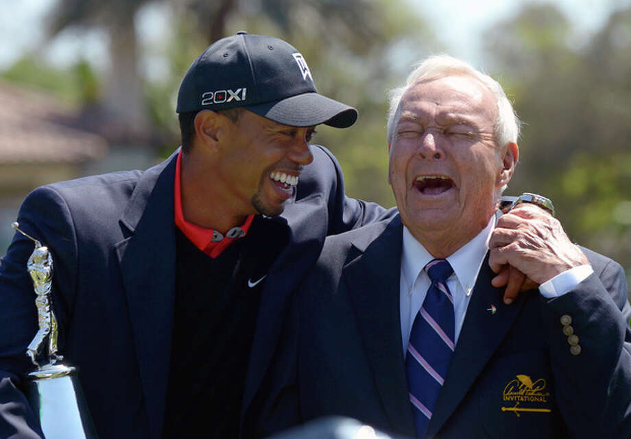 Tiger Woods, left, and Arnold Palmer share a laugh during the trophy presentation after Woods won the Arnold Palmer Invitational golf tournament in Orlando, Fla., Monday, March 25, 2013. (AP Photo/Phelan M. Ebenhack) / FR121174 AP