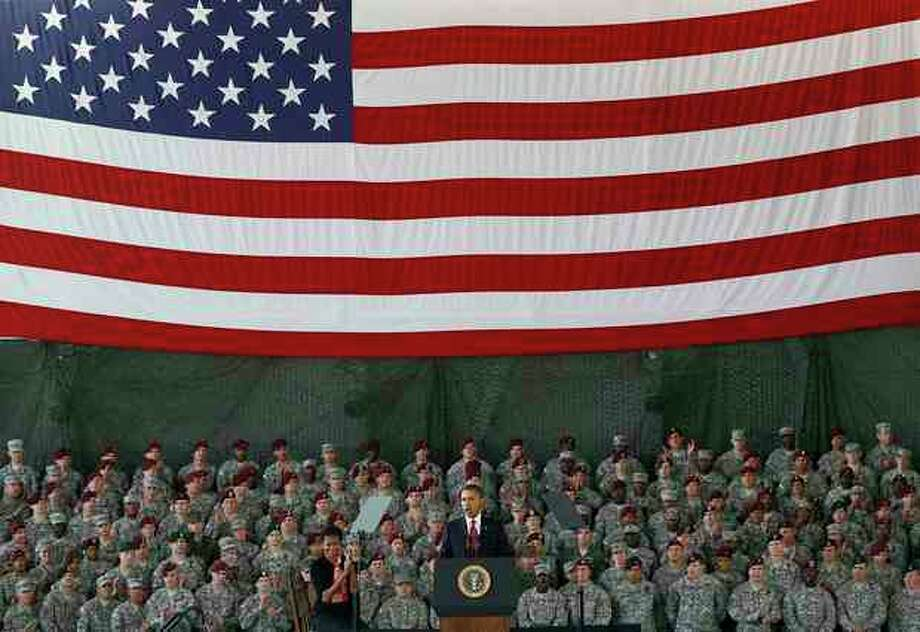 FILE - In this Dec. 14, 2011 file photo, President Barack Obama, accompanied by first lady Michelle Obama, speaks to troops at Fort Bragg, N.C. For now, there are no plans to hold a huge ticker-tape parade for troops returning from Iraq, no arrangements for a grand, flag-waving, red-white-and-blue homecoming of the sort America's fighting men and women received after World War II and the Gulf War. Instead, most welcomes have been smaller-scale: hugs from families at military posts across the country, a somber commemoration by President Barack Obama at Fort Bragg. (AP Photo/Gerry Broome, File) / AP