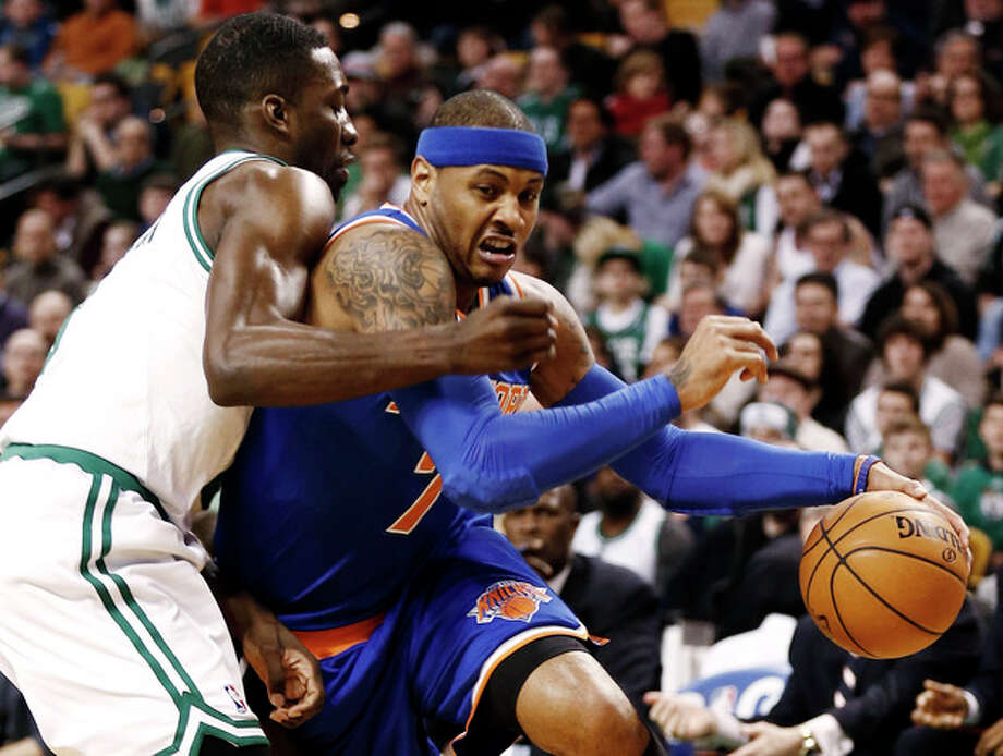 New York Knicks' Carmelo Anthony, right, drives on Boston Celtics' Jeff Green during the first quarter of an NBA basketball game in Bostonn Tuesday, March 26, 2013. (AP Photo/Winslow Townson) / FR170221 AP