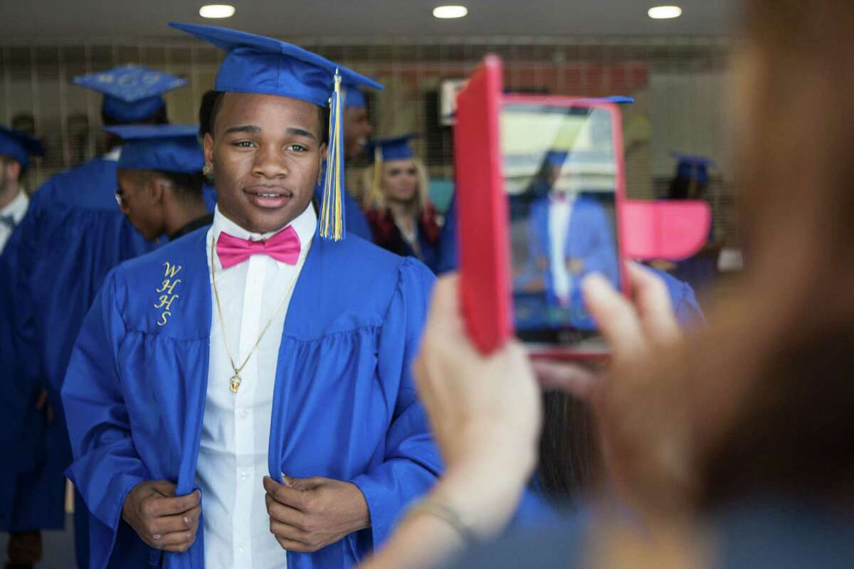 Jeffrey Rogers get his photo taken by Helen Longo, Medical Assistant for Optimus Healthcare School Based Health Center at Harding before the 90th Annual Commencement Ceremony for Warren Harding High School took place at Webster Bank Arena in Bridgeport, Conn. on Tuesday, June 14, 2016.