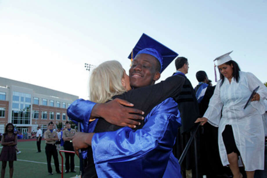 Mckervin Edwine Ceme smiles he hugs Principal Koroshetz after recieving his diploma during Brien McMahon's 51st Commencement Excercise held Friday evening.Hour Photo / Danielle Robinson