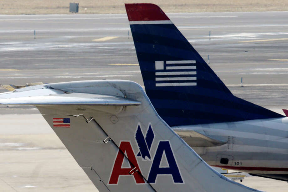 FILE - American Airlines and US Airways jets prepare for flight at gate at the Philadelphia International Airport, in this Feb. 14, 2013 file photo taken in Philadelphia. The merger of US Airways and American Airlines has been arroved by the bankruptcy court Wednesday March 27, 2013 giving birth to a mega airline with more passengers than any other in the world. (AP Photo/Matt Rourke) / AP