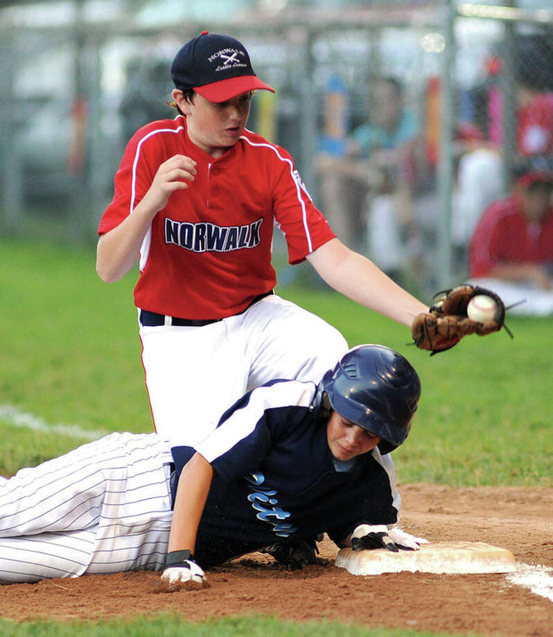 hour photo/John Nash - Norwalk first baseman John Swick, top, comes up with the ball after Wilton's Michael Tienken dove back safely into first on a pick-off attempt.