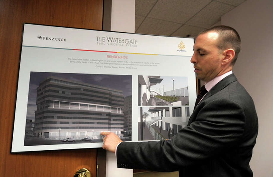 In this photo taken May 30, 2012, Penzance Senior Vice President of Leasing Matthew Pacinelli shows a rendering of the planned renovations for the front of the Watergate Office Building in Washington. Forty years ago police in Washington arrested five men breaking in to the Democratic National Committee offices in Washington. The name of the complex they were breaking into became infamous: the Watergate. These days, though, unless you know where to look, there's little marking the location of the 1972 crime that ultimately led to the resignation of President Richard Nixon. The office building that was the site of the break in is still in use, though the tenants have changed. The adjacent hotel where the burglars stayed is currently closed. And another hotel across the street where a lookout waited with a walkie-talkie, monitoring the burglars' progress, has been turned into a college dorm. (AP Photo/Susan Walsh) / AP