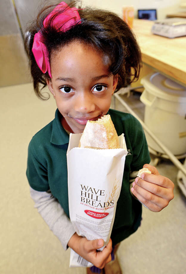 "Side by Side's kindergartner Zoe McLean has a taste of a bagette as her class visits the new Wave Hill Bakery and Café to learn how to bake bread, as part of their ""bread"" study Wednesday morning. Hour photo / Erik Trautmann / (C)2013, The Hour Newspapers, all rights reserved"