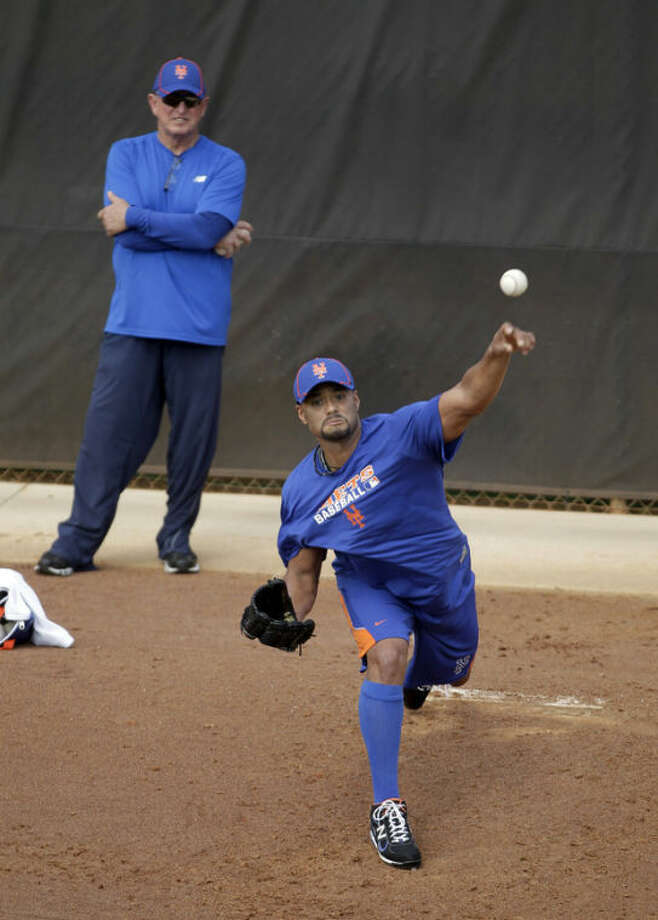 In this Feb. 17, 2012, photo, New York Mets pitcher Johan Santana throws a bullpen session as pitching coach Dan Warthen watches during spring training baseball in Port St. Lucie, Fla. The Mets say Santana has injured his left shoulder again and likely will need surgery and miss the 2013 season. The two-time Cy Young Award winner missed the 2011 season following shoulder surgery in September 2010, then returned last year and pitched the first no-hitter in the team's history. He hasn't pitched in an exhibition game in 2013 because of arm weakness. (AP Photo/Jeff Roberson)
