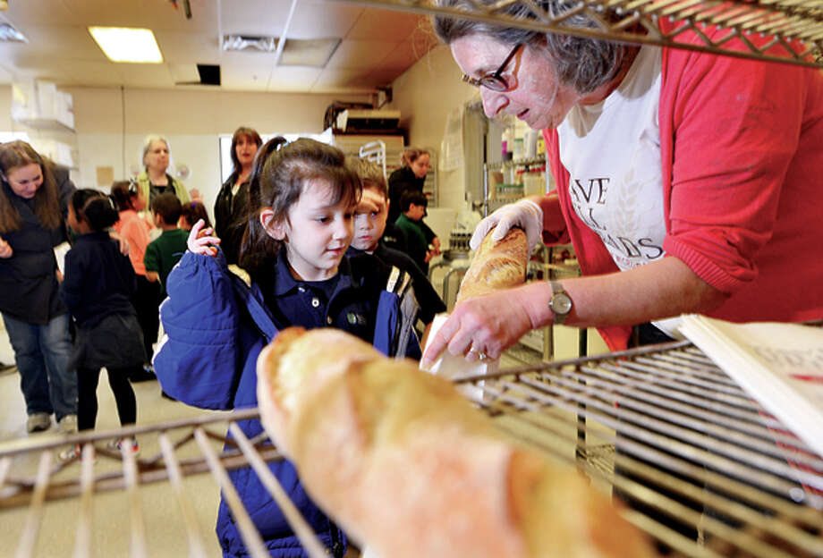 """Side by Side's kindergartner Mia Sutton recieves a bagette from bakery owner Margaret Sapir as her class visits the new Wave Hill Bakery and Café to learn how to bake bread, as part of their """"bread"""" study Wednesday morning. Hour photo / Erik Trautmann / (C)2013, The Hour Newspapers, all rights reserved"""