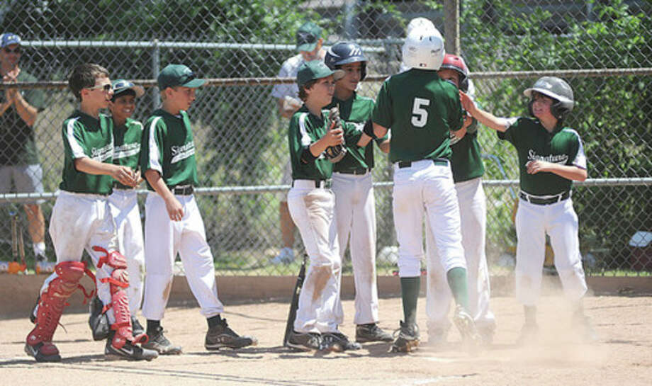 Hour photo/John NashSignature Landscaping's Dax Generaso (5) is congratulated at home plate by teammates after hitting a two-run home run in Saturday's Norwalk Little League Majors Division championship game at Broad River Field. Signature took the title with a 9-2 victory over top-seeded Laurel A.C.