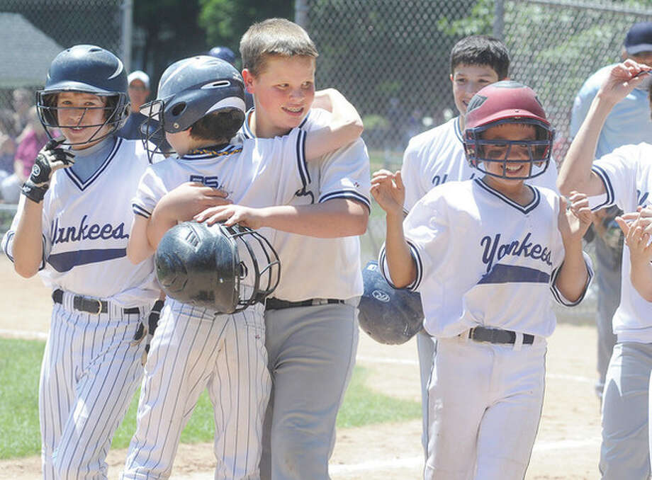 Hour Photo/Matthew VinciMatt Fair of the Yankees, center, is greeted at home by teammates after hitting a grand slamhome run in the Westport Little League Majors Division championship game. The Yanks won, 14-8