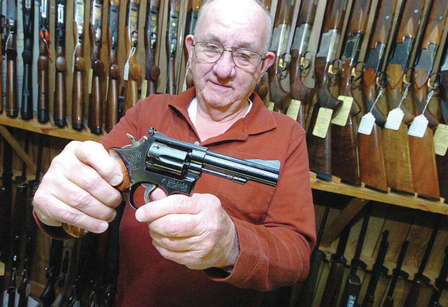 Hour photo / Alex von KleydorffBob Montlick, owner of Bob's Gun Exchange, shows one of the more popular handguns, a Smith and Wesson Model 19. / 2013 The Hour Newspapers