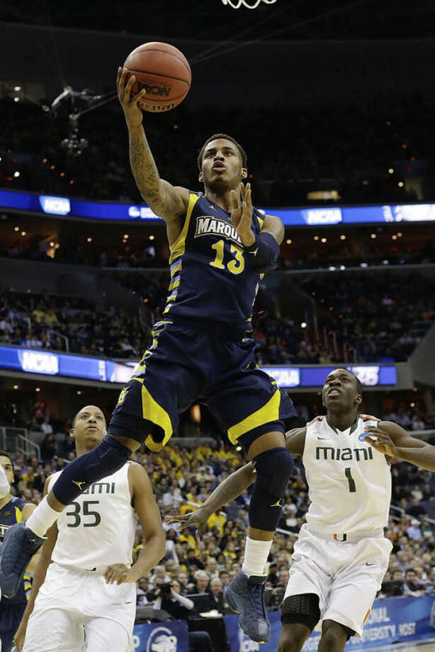 Marquette guard Vander Blue (13) shoots past Miami forward Kenny Kadji (35), and guard Durand Scott (1) during the first half of an East Regional semifinal in the NCAA college basketball tournament on Thursday, March 28, 2013, in Washington. (AP Photo/Pablo Martinez Monsivais)