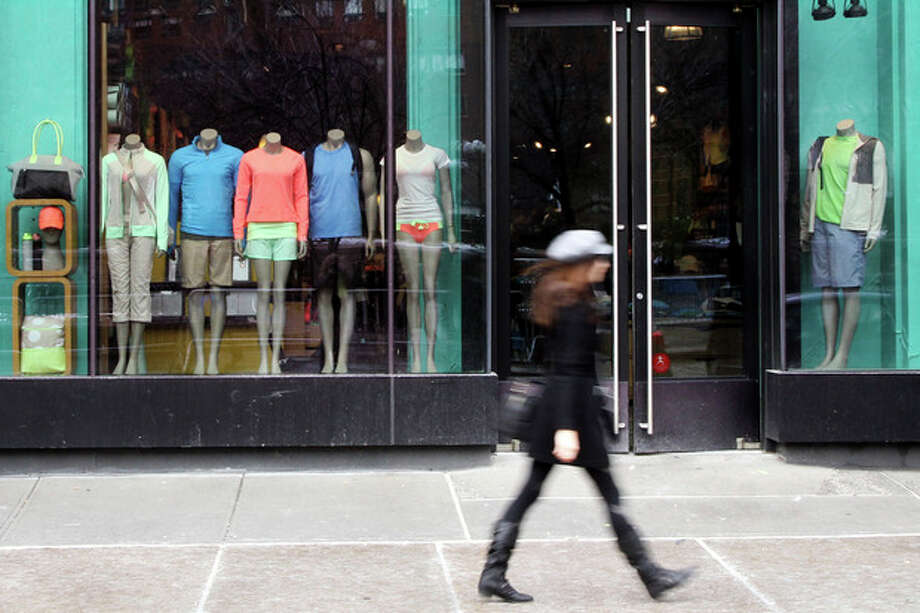 FILE - In this Tuesday, March 19, 2013 file photo, a woman walks past the Lululemon Athletica store at Union Square in New York. Lululemon says no demonstrations of yoga positions or otherwise are needed to return its pricey black yoga pants that the company pulled from shelves for being too sheer. The yoga gear maker's policy statement comes after a New York Post report that was widely circulated by the media recounted one woman's tale of being asked to bend over when trying to return some pants to prove they were sheer. (AP Photo/Mary Altaffer) / AP