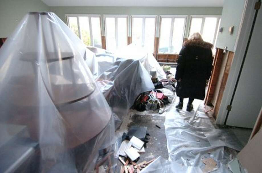 Photo/Alex von Kleydorff. Clear plastic tarps shroud all the personal items in the living room as homeowner Joan Shwartz surveys the flood damaged house on Woods Cove Rd in Westport Wednesday.