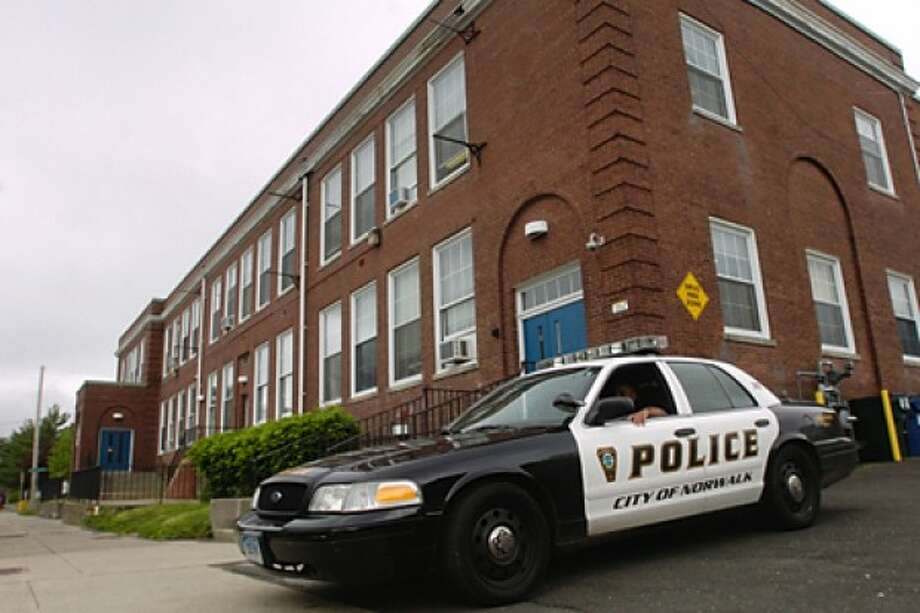 A Norwalk police cruiser sits outside Columbus Magnet School following a strings a of shootings on Chesnut St. in South Norwalk. Hour photo / Erik Trautmann