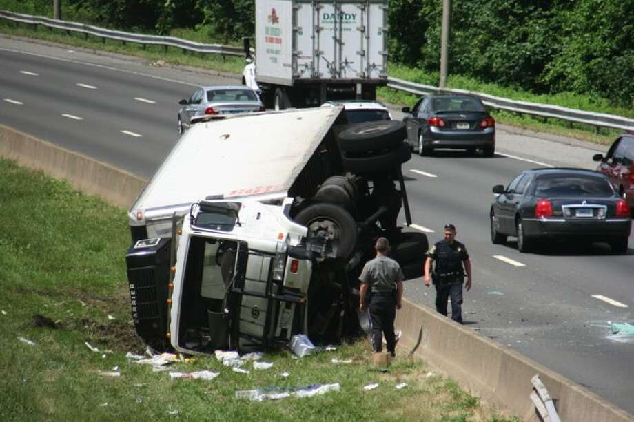 State police check the scene of a truck rollover on I-95 near exit 16 on Monday morning.