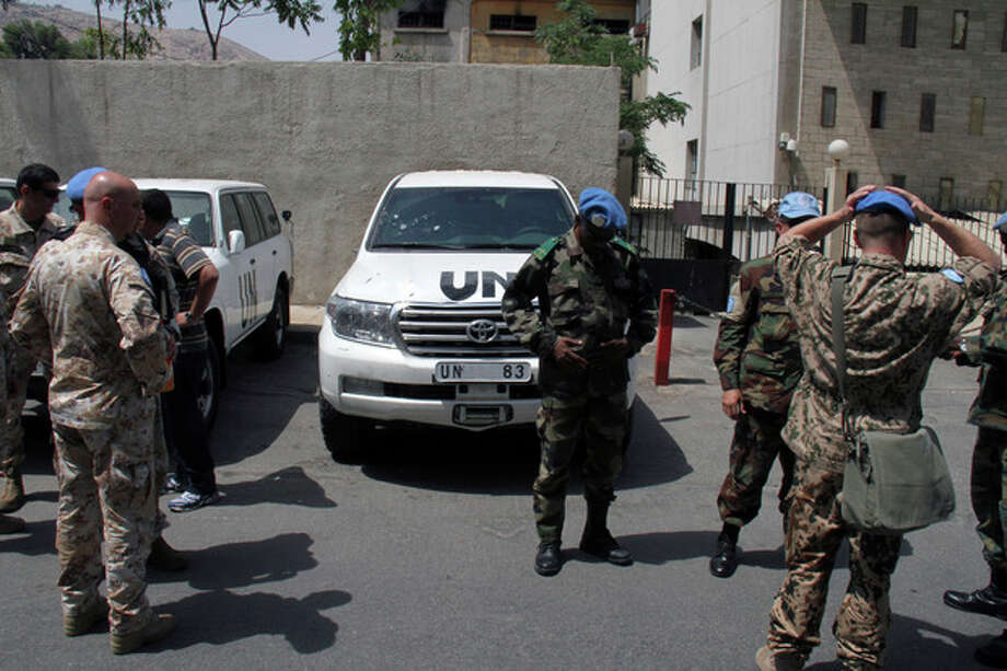 U.N. observers welcome their comrades upon their return from al-Haffa, in northern Syria, to Damascus, Syria, on Saturday, June 16, 2012. U.N. observers in Syria suspended their activities and patrols Saturday because of escalating violence in the country, the head of the mission said, the strongest sign yet that an international peace plan for Syria is disintegrating. (AP Photo/Bassem Tellawi) / AP