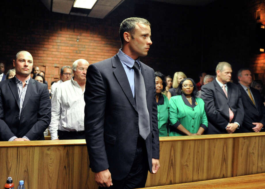 FILE - In this Feb. 19, 2013 file photo, olympian Oscar Pistorius stands following his bail hearing in Pretoria, South Africa. A judge in South Africa says Pistorius, who is charged with murdering his girlfriend, can leave South Africa to compete in international competition, with conditions. (AP Photo/File) / AP