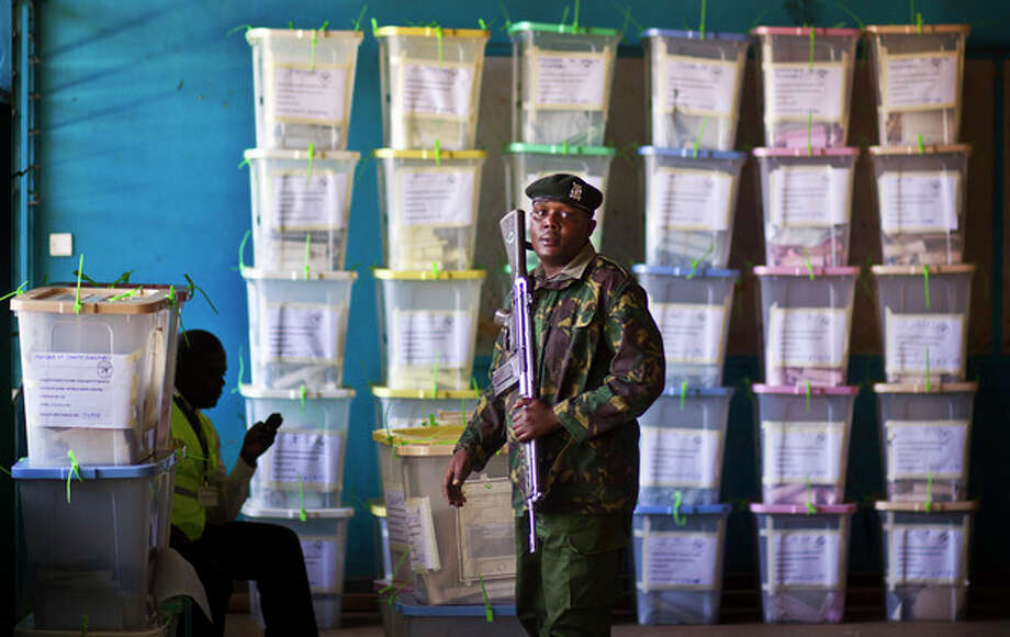FILE - In this Tuesday, March 5, 2013 file photo, an officer of the prisons service helps to carry ballot boxes for stacking after their results were tallied, at a vote tallying center in Nairobi, Kenya. Vote totals for Kenya's president-elect mysteriously increased between the time the ballot numbers were announced at some remote polling centers and when they reached the national tallying center in the capital, a lawyer for a civil society group told the country's Supreme Court on Wednesday, March 27, 2013. (AP Photo/Ben Curtis, File) / AP