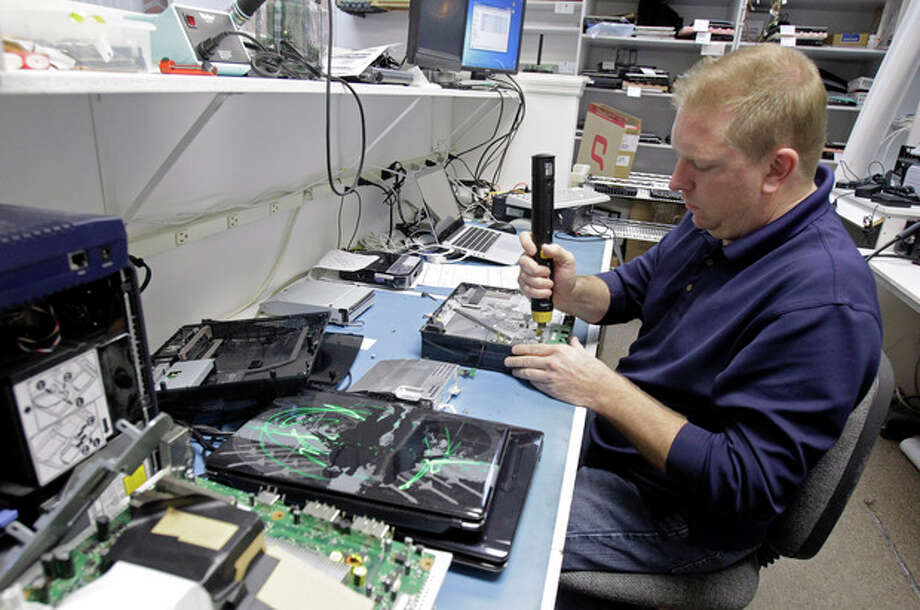 Technician Shawn Cable repairs a video game console at the Laptops Plus computer store in Winter Park, Fla., Thursday, Jan. 5, 2012. A burst of hiring in December pushed the unemployment rate to its lowest level in nearly three years, giving the economy a boost at the end of 2011. (AP Photo/John Raoux) / AP