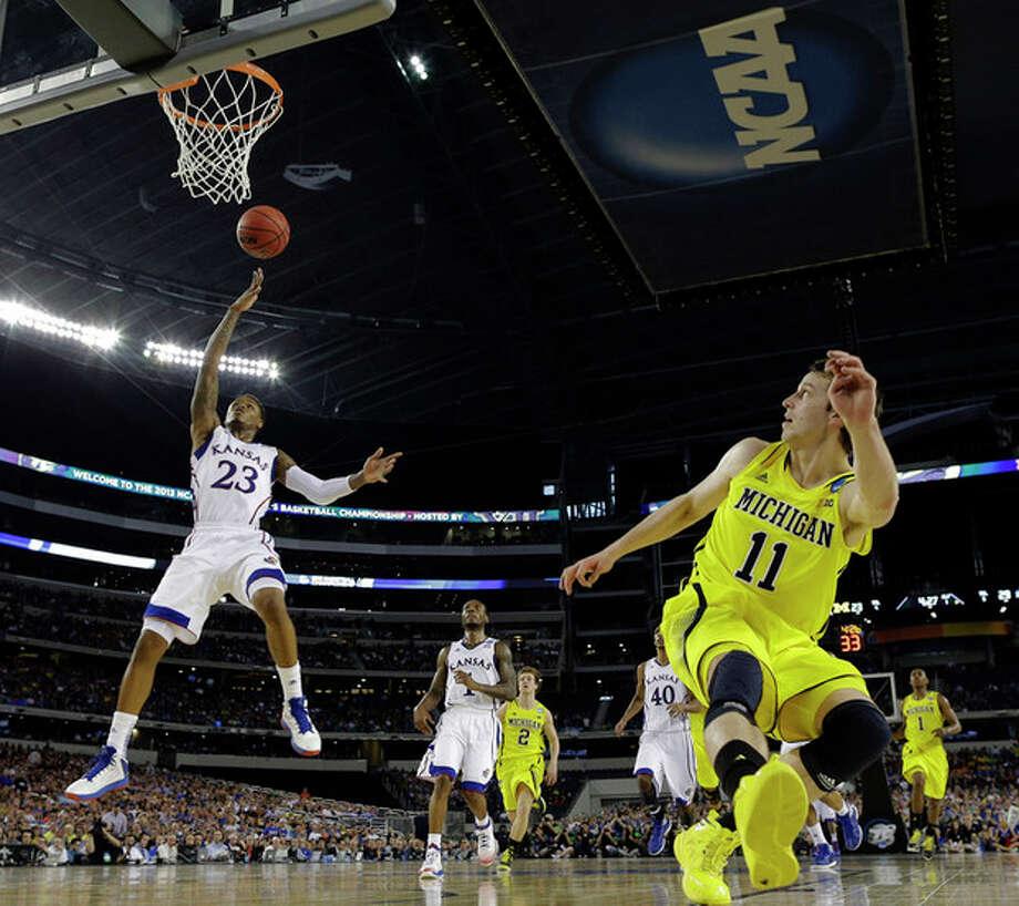 Kansas' Ben McLemore shoots over Michigan's Nik Stauskas during the first half of a regional semifinal game in the NCAA college basketball tournament, Friday, March 29, 2013, in Arlington, Texas. (AP Photo/David J. Phillip) / AP