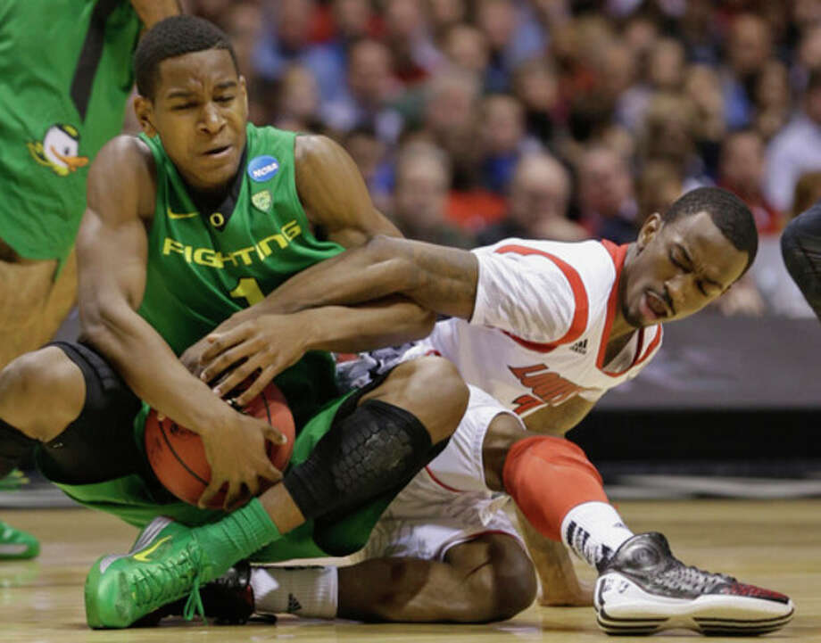 Oregon guard Dominic Artis (1) and Louisville guard Russ Smith scramble for a loose ball during the second half of a regional semifinal in the NCAA college basketball tournament, Friday, March 29, 2013, in Indianapolis. (AP Photo/Darron Cummings) / AP