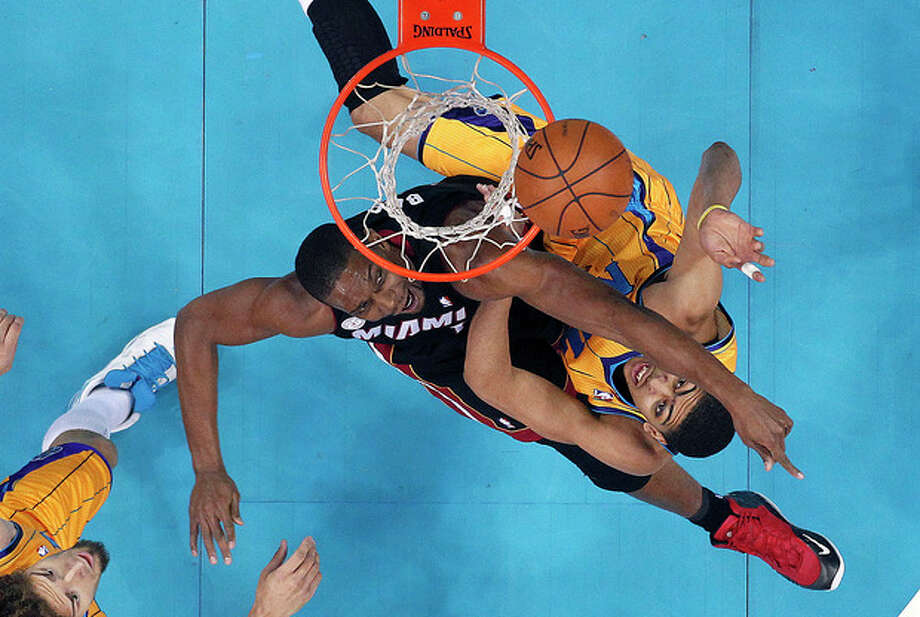 Miami Heat center Chris Bosh, top left, tries to block a shot by New Orleans Hornets forward Anthony Davis in the first half of an NBA basketball game in New Orleans, Friday, March 29, 2013. (AP Photo/Gerald Herbert) / AP