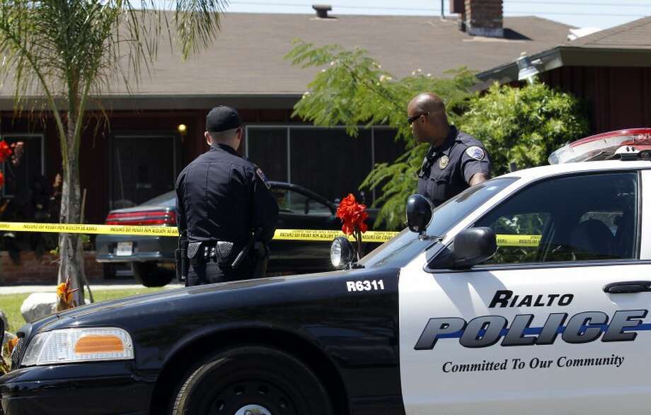 Two police officers stand in front of Rodney King's home in Rialto, Calif., Sunday, June 17, 2012. King, the black motorist whose 1991 videotaped beating by Los Angeles police officers was the touchstone for one of the most destructive race riots in U.S. history, died Sunday. He was 47. King's fiancee called police at 5:25 a.m. to report that she found him at the bottom of the swimming pool at their home in Rialto, California, police Lt. Dean Hardin said. (AP Photo/Jae C. Hong)