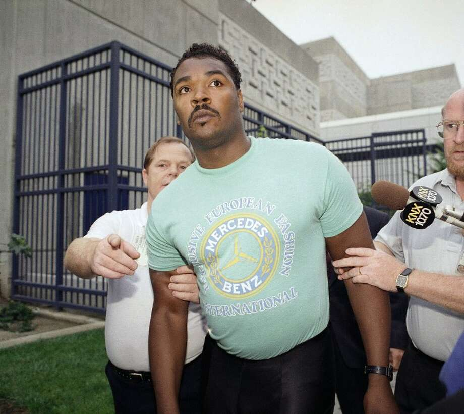 FILE - This July 16, 1992 file photo shows Rodney King being escorted from jail in Santa Ana, Calif. after he was arrested for investigation of drunken driving. King, whose videotaped beating by police in 1991 led to LA race riots, has died at 47. (AP Photo/Kevork Djansezian, file)
