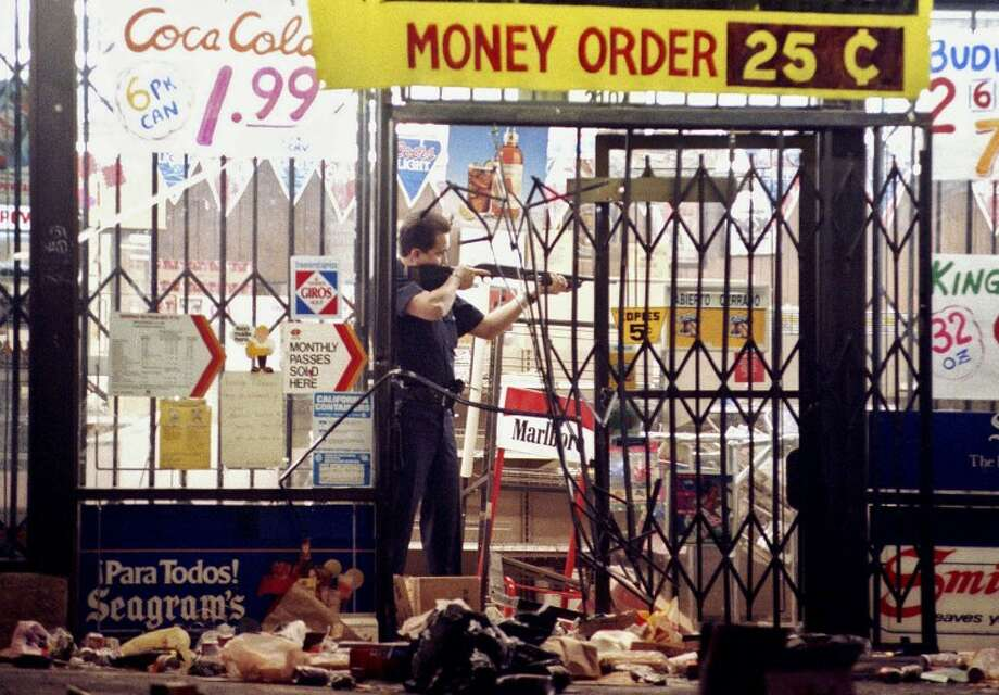 FILE - In this April 30, 1992 file photo, a Los Angeles police officer takes aim at a looter in a market at Alvarado and Beverly Boulevard in Los Angeles during the second night of rioting in the city. Rodney King, the black motorist whose 1991 videotaped beating by Los Angeles police officers was the touchstone for one of the most destructive race riots in the nation's history, has died, his publicist said Sunday, June 17, 2012. He was 47.(AP Photo/John Gaps III, File)