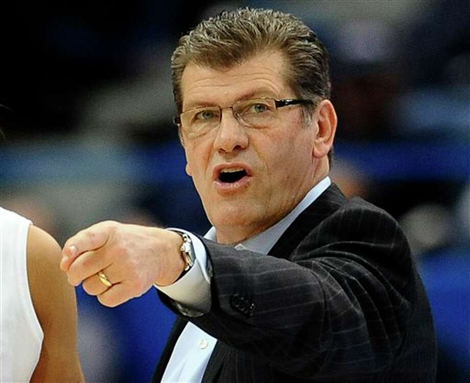 FILE - In this March 11, 2013, file photo, Connecticut head coach Geno Auriemma talks with players during the first half of an NCAA college basketball game against Syracuse in the semifinals of the Big East Conference tournament in Hartford, Conn. Auriemma has signed a new $10.86 million contract, a deal designed to keep him at the school through the 2017-18 season, UConn announced Wednesday, March 27, 2013. (AP Photo/Jessica Hill, File) / FR125654 AP
