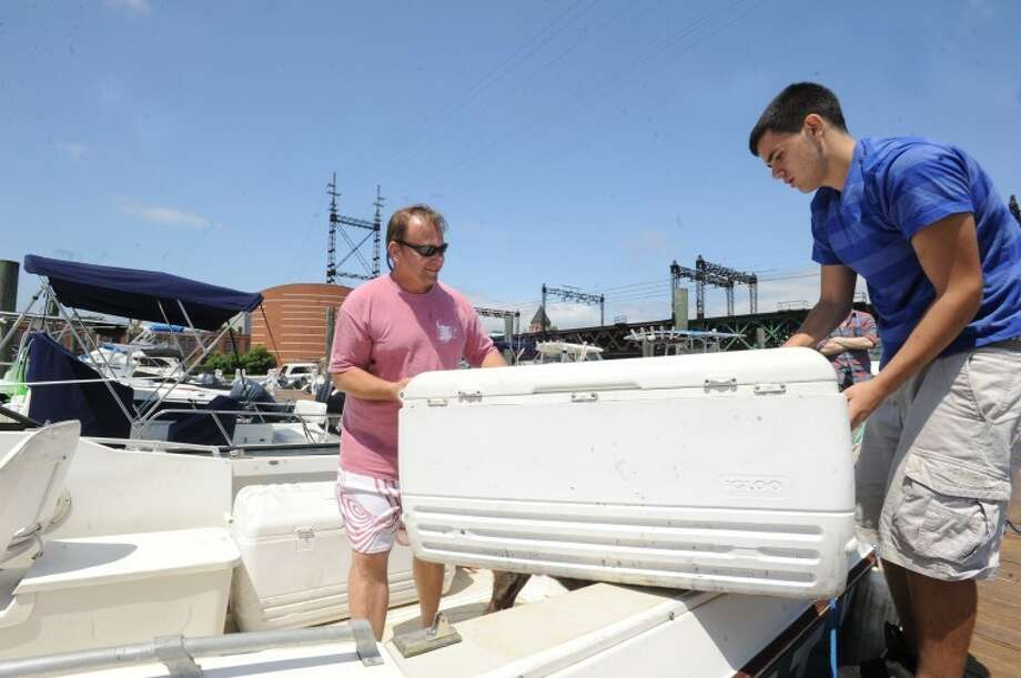 Clyde Ripka, owner of Bulls Head Market and employee Ryan Davis load the Food Boat Sunday serving, ice cream, seafood, ice and mixers to boats on the waters in the area. hour photo/Matthew Vinci
