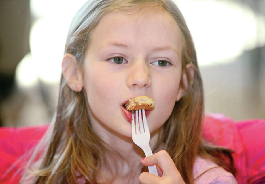 Emily Beggs, 8, eats breakfast at the Brien McMahon High School girls' soccer team Pancake Breakfast Fundraiser and Easter Egg Hunt Saturday at the Center for Global Studies. Hour photo / Erik Trautmann / (C)2013, The Hour Newspapers, all rights reserved