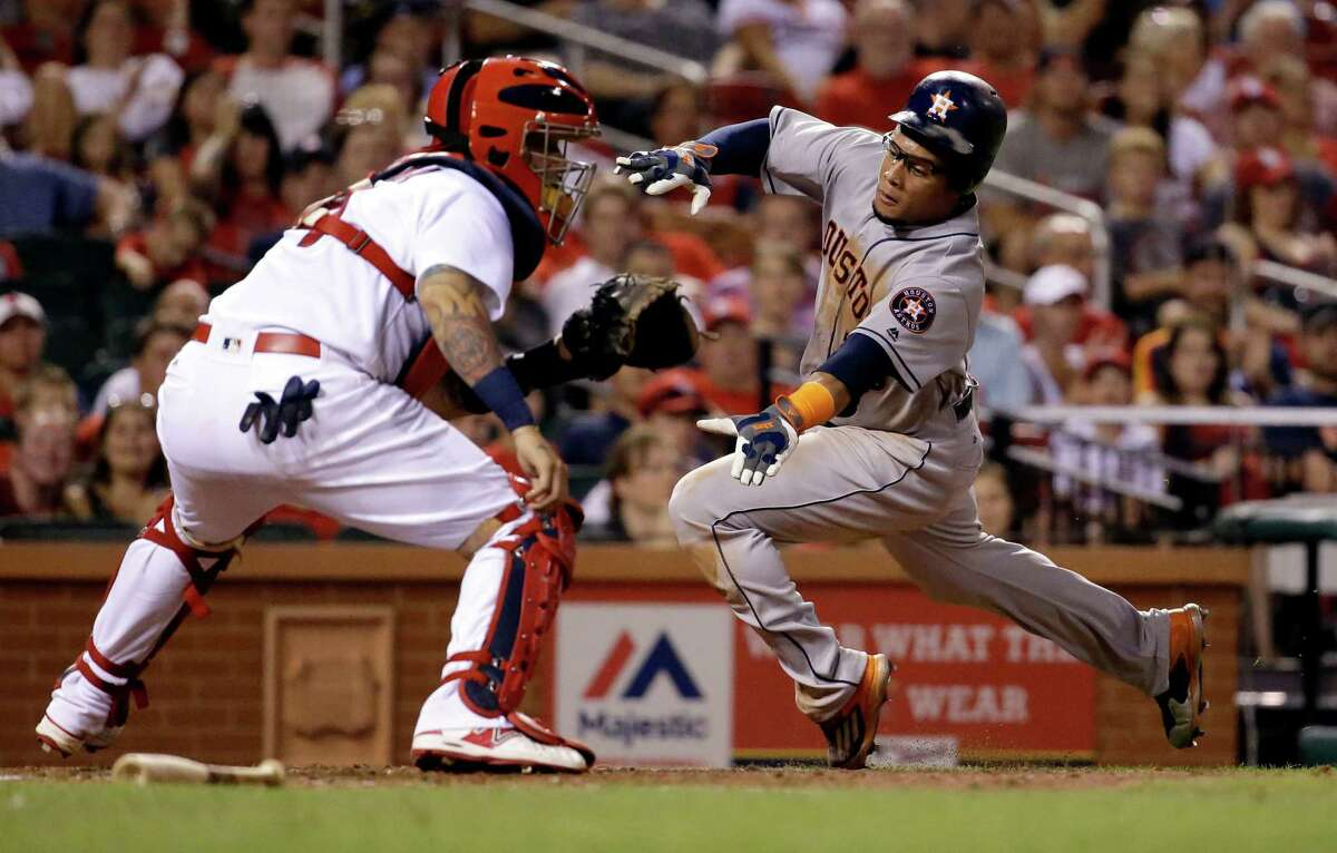 Houston Astros' Carlos Gomez, right, scores past St. Louis Cardinals catcher Yadier Molina during the seventh inning of a baseball game Tuesday, June 14, 2016, in St. Louis. (AP Photo/Jeff Roberson)
