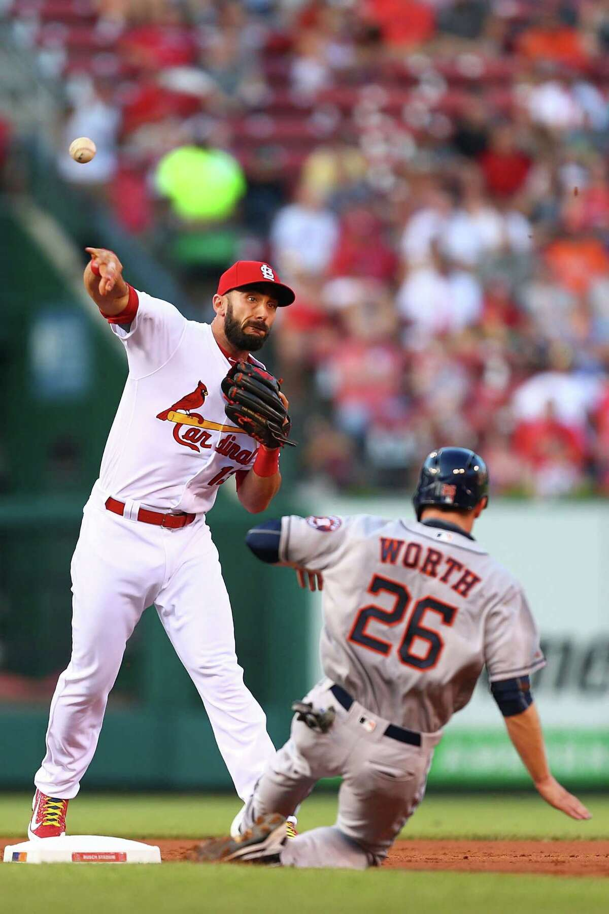 ST. LOUIS, MO - JUNE 14: Matt Carpenter #13 of the St. Louis Cardinals turns a double play over Danny Worth #26 of the Houston Astros in the first inning at Busch Stadium on June 14, 2016 in St. Louis, Missouri.