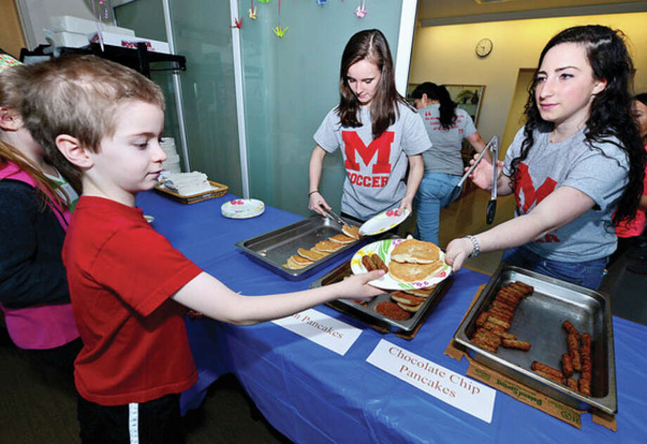 Hour photo / Erik TrautmannAbove, Brien McMahon High School girls' soccer teammates Laura Linehan and Gianna Bazzano serve up breakfast to 7-year-old Daniel Chironna at their Pancake Breakfast Fundraiser and Easter Egg Hunt Saturday at the Center for Global Studies. Middle, Carly Cambareri, 7, finds an egg. Bottom, Taem Kaplan, 2, displays an egg he hunted. / (C)2013, The Hour Newspapers, all rights reserved