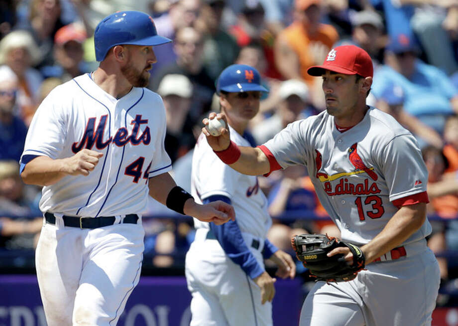 New York Mets' John Buck, left, is tagged out by St. Louis Cardinals third baseman Matt Carpenter after being caught between third and home during the fourth inning of an exhibition spring training baseball game, Friday, March 29, 2013, in Port St. Lucie, Fla. (AP Photo/Jeff Roberson) / AP