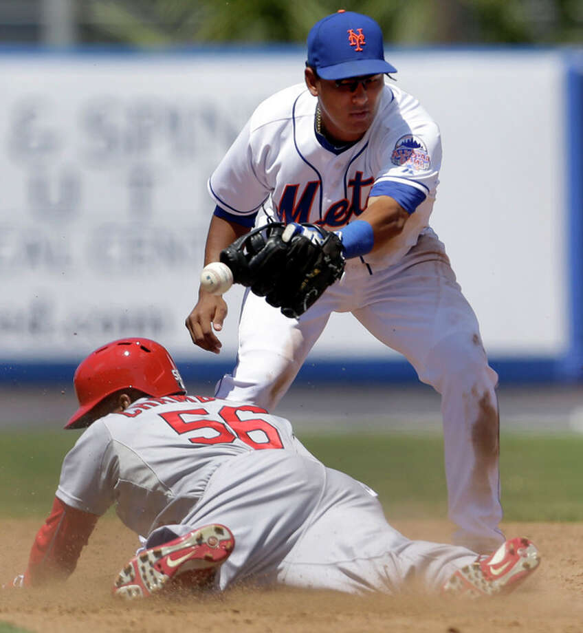 St. Louis Cardinals' Adron Chambers, bottom, is safe at second for a two-run double as the throw gets away from New York Mets shortstop Ruben Tejada during the fifth inning of an exhibition spring training baseball game Friday, March 29, 2013, in Port St. Lucie, Fla. (AP Photo/Jeff Roberson) / AP