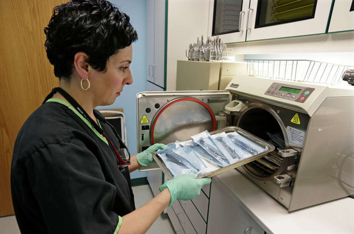 Dentist Alice G. Boghosian removes packages of properly sterilized dental instruments from an autoclave that uses heat and steam to sterilize the tools Friday, March 29, 2013, in Chicago. Health officials in Oklahoma are calling an oral surgeon there who used dirty equipment and risked cross-contamination a ?