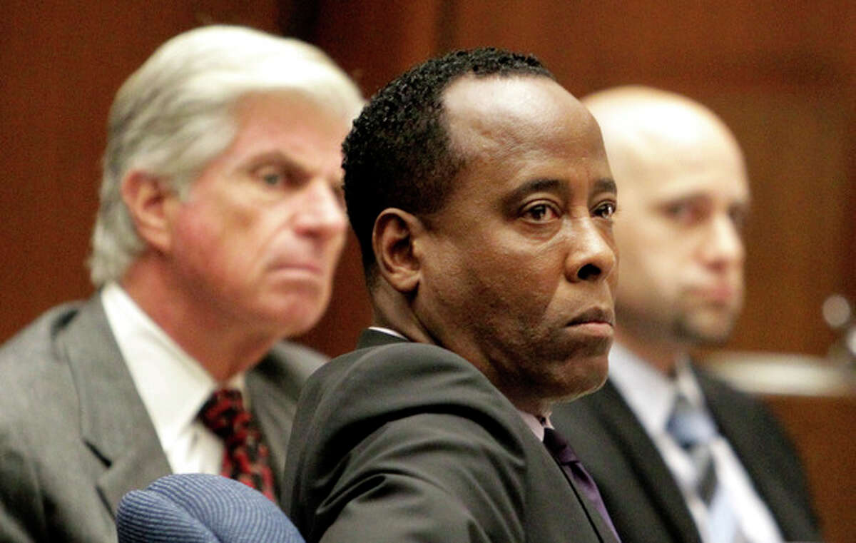Dr. Conrad Murray, center, looks on beside his lawyers J. Michael Flanagan, left, and Nareg Gourjian during Murray's involuntary manslaughter trial, Wednesday, Oct. 19, 2011, in downtown Los Angeles. Murray has pleaded not guilty and faces four years in prison and the loss of his medical license if convicted of involuntary manslaughter in Michael Jackson's death. (AP Photo/Reed Saxon, Pool)