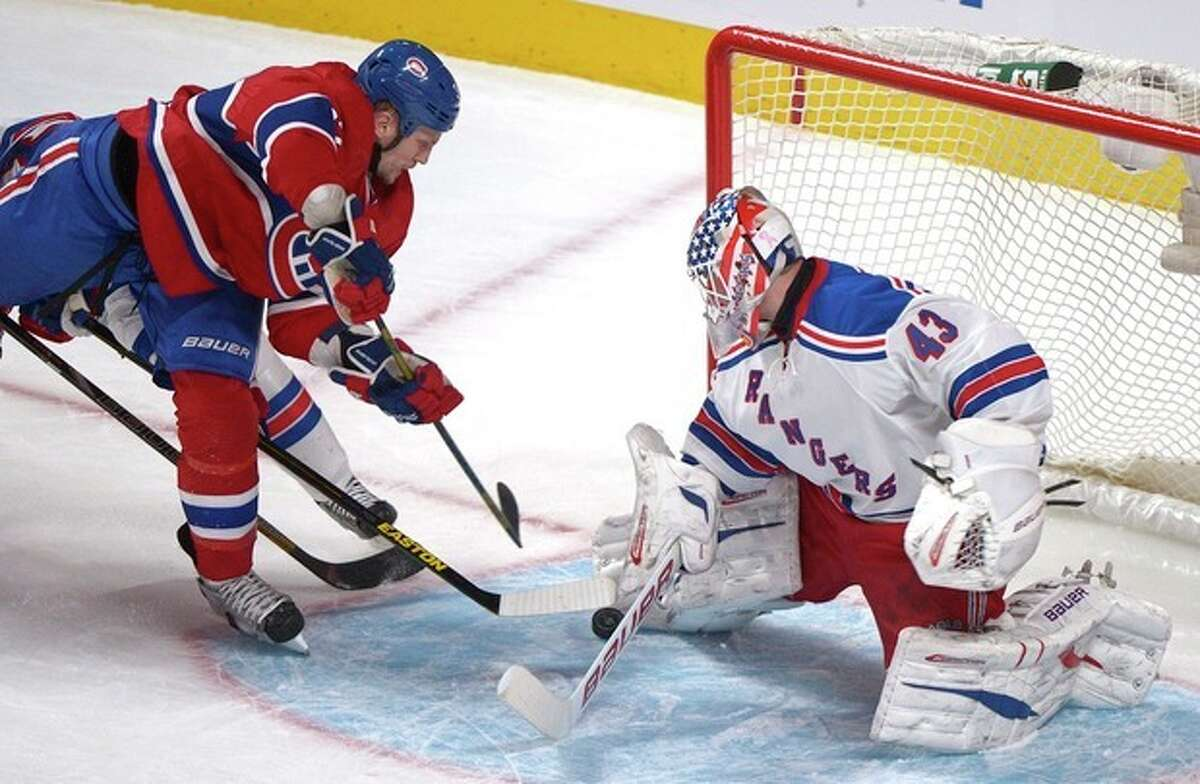 Montreal Canadiens' Travis Moen, left, moves in on New York Rangers goaltender Martin Biron, right, during second-period NHL hockey game action in Montreal, Saturday, March 30, 2013. (AP Photo/The Canadian Press, Graham Hughes)