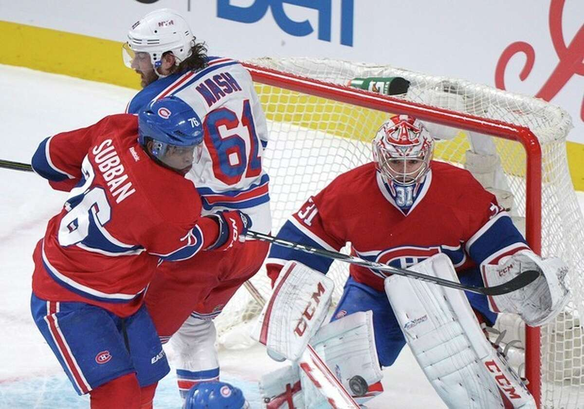 Montreal Canadiens goaltender Carey Price, right, makes a save against New York Rangers' Rick Nash as Canadiens' P.K. Subban (76) defends during first-period NHL hockey game action in Montreal, Saturday, March 30, 2013. (AP Photo/The Canadian Press, Graham Hughes)