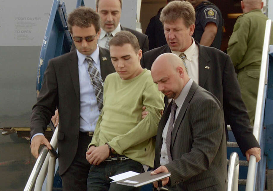 In this photo provided by Montreal Police, Luka Rocco Magnotta is taken by police from a Canadian military plane to a waiting van on Monday, June 18, 2012, in Mirabel, Quebec. Magnotta, the suspect in the killing and dismemberment of a Chinese student, returned to Canada via military transport from Germany, where he was arrested this month. (AP Photo/Montreal Police) / Montreal Police
