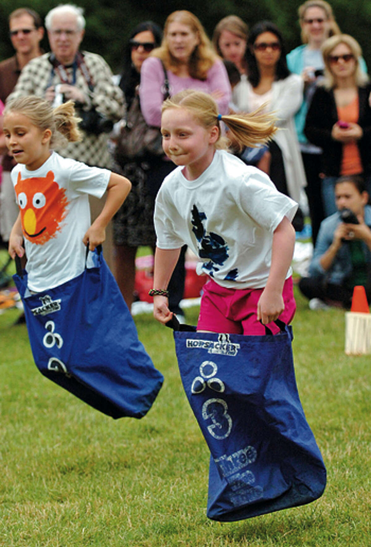 Miller Driscoll first graders Heather Plowright and Sloane Sullivan participate in the sack race during the school's field day Tuesday morning. Hour photo / Erik Trautmann
