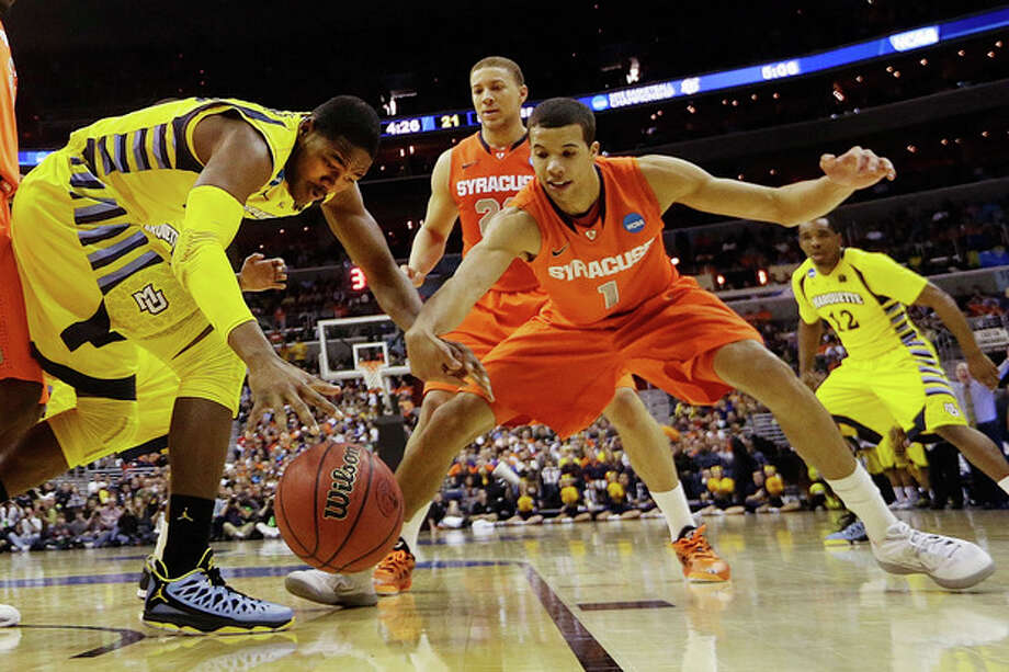 Marquette forward Steve Taylor Jr., (25) and Syracuse guard Michael Carter-Williams (1) reach for a loose ball during the first half of the East Regional final in the NCAA men's college basketball tournament, Saturday, March 30, 2013, in Washington. (AP Photo/Pablo Martinez Monsivais) / AP